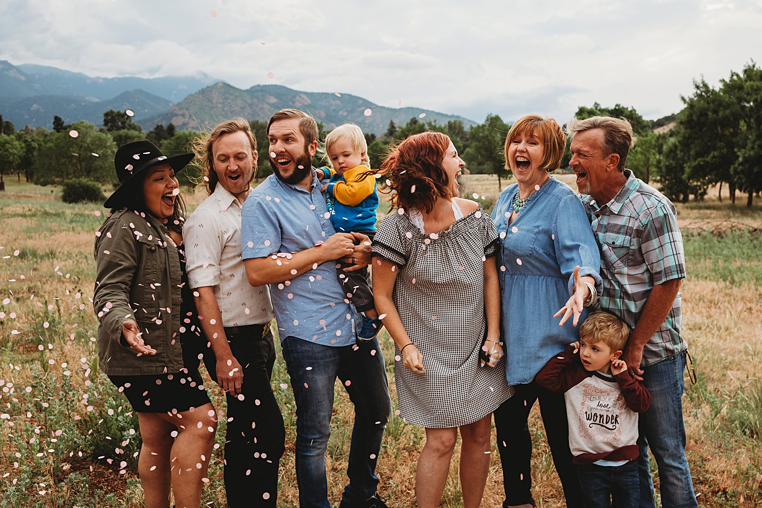 Extended family popping a gender reveal balloon