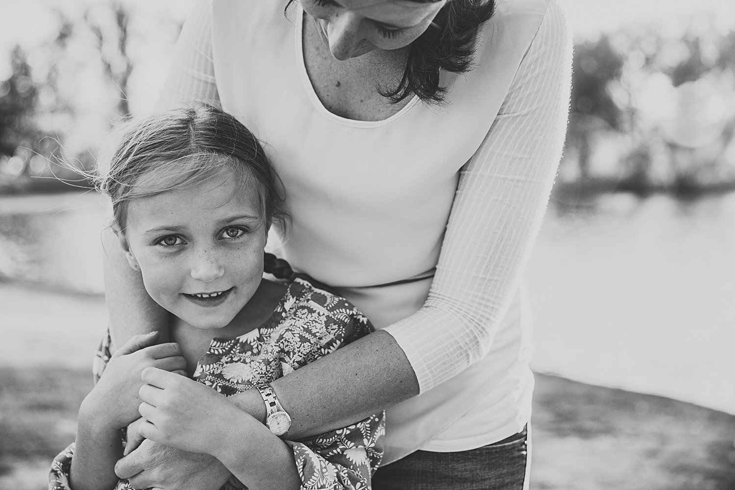 Young girl being hugged from behind by mom