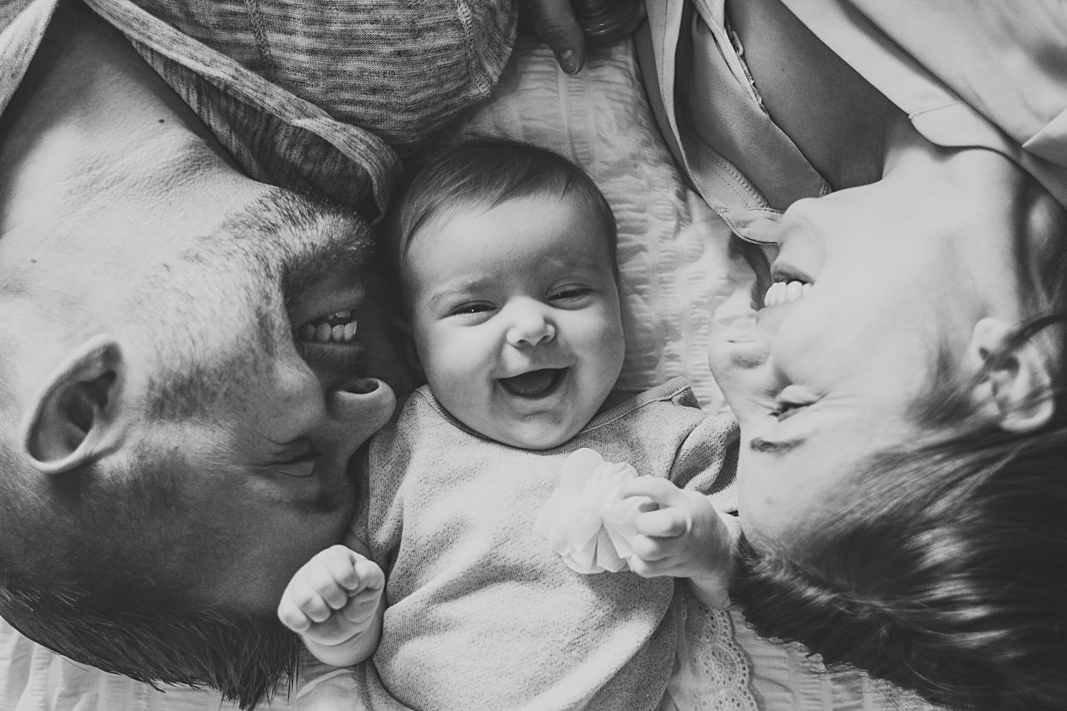 Laughing baby between mom and dad laying on bed