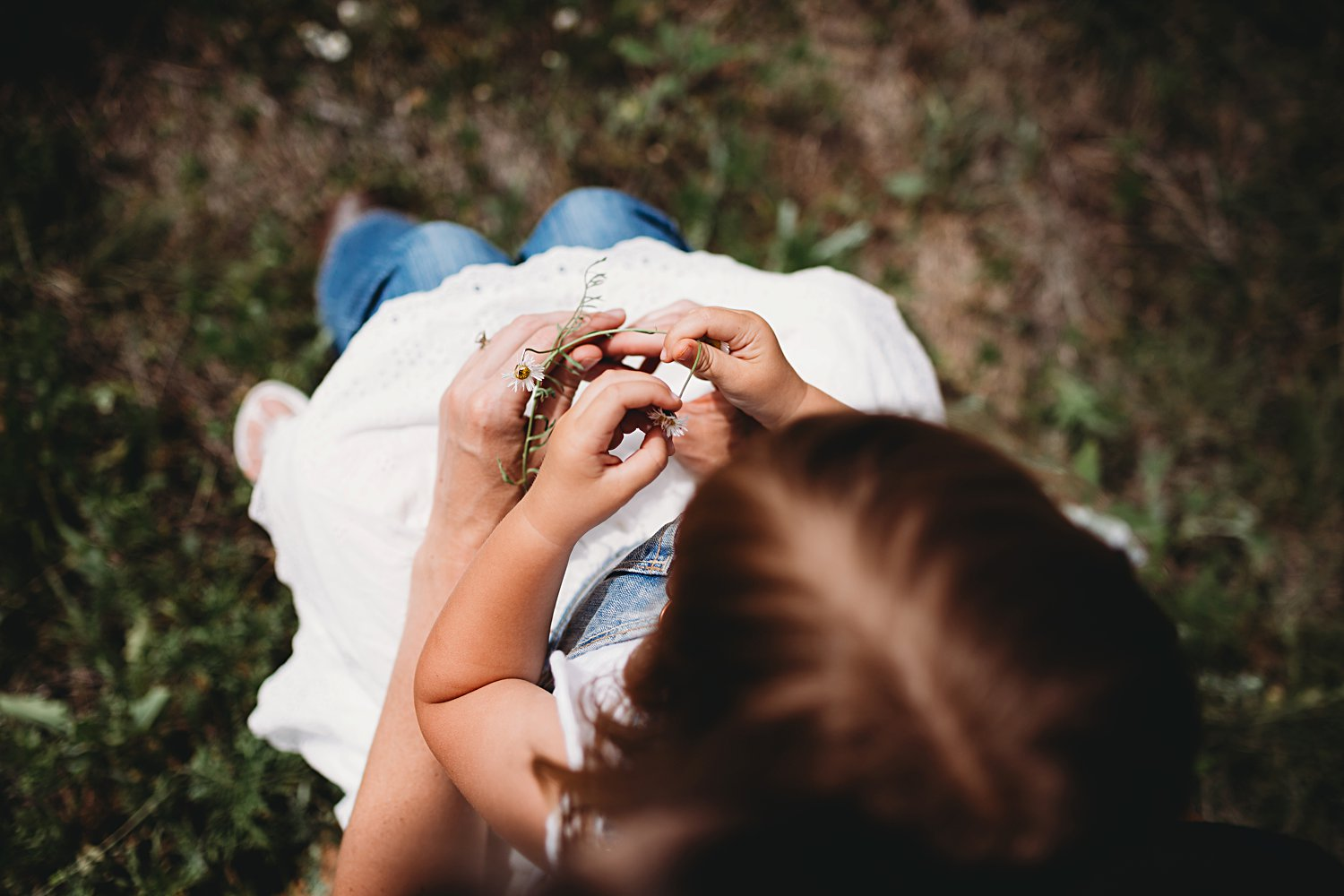 Mom holds young daughter in lap and play with flowers