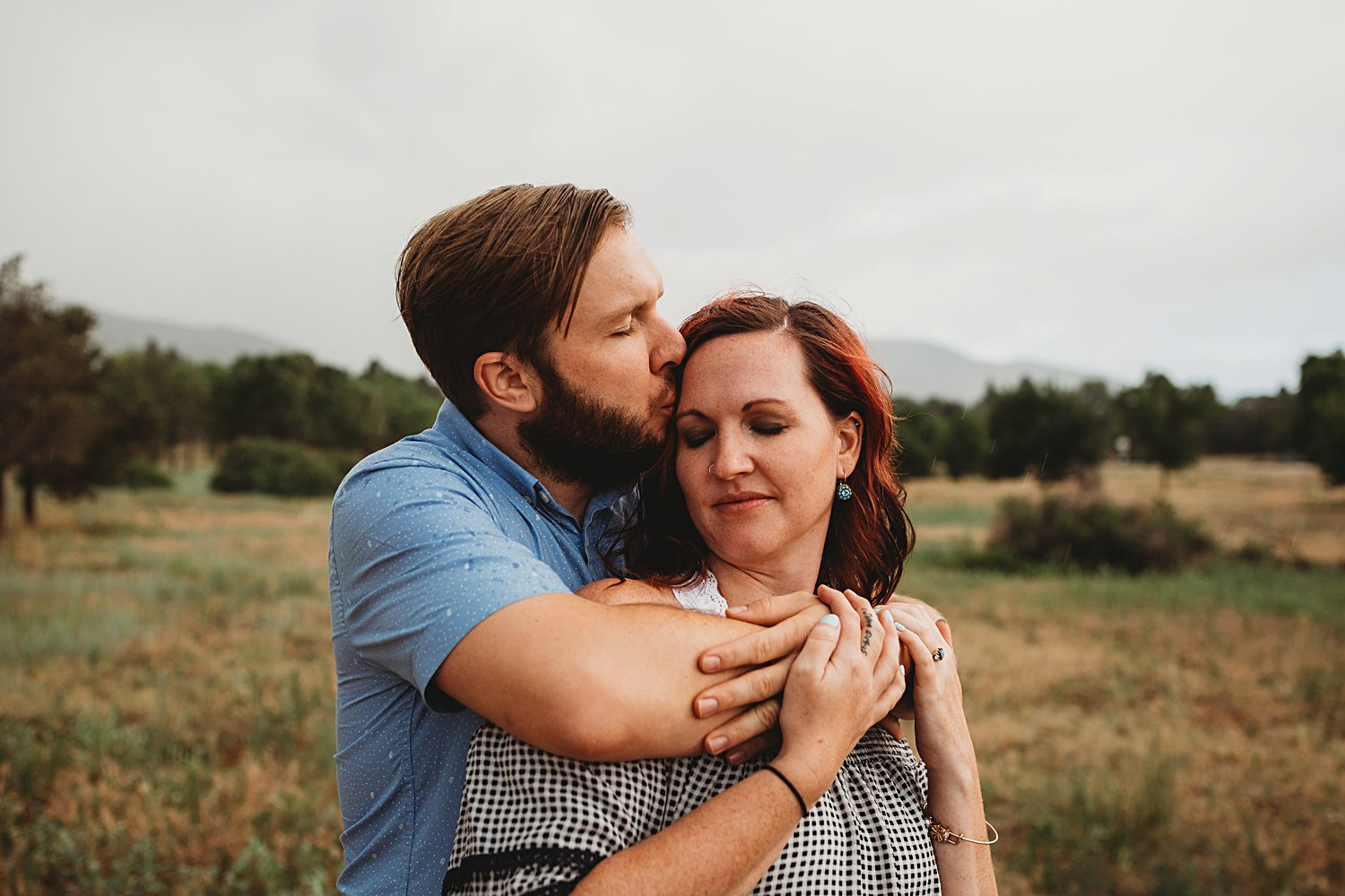 Man embraces wife and gives her a kiss on the cheek