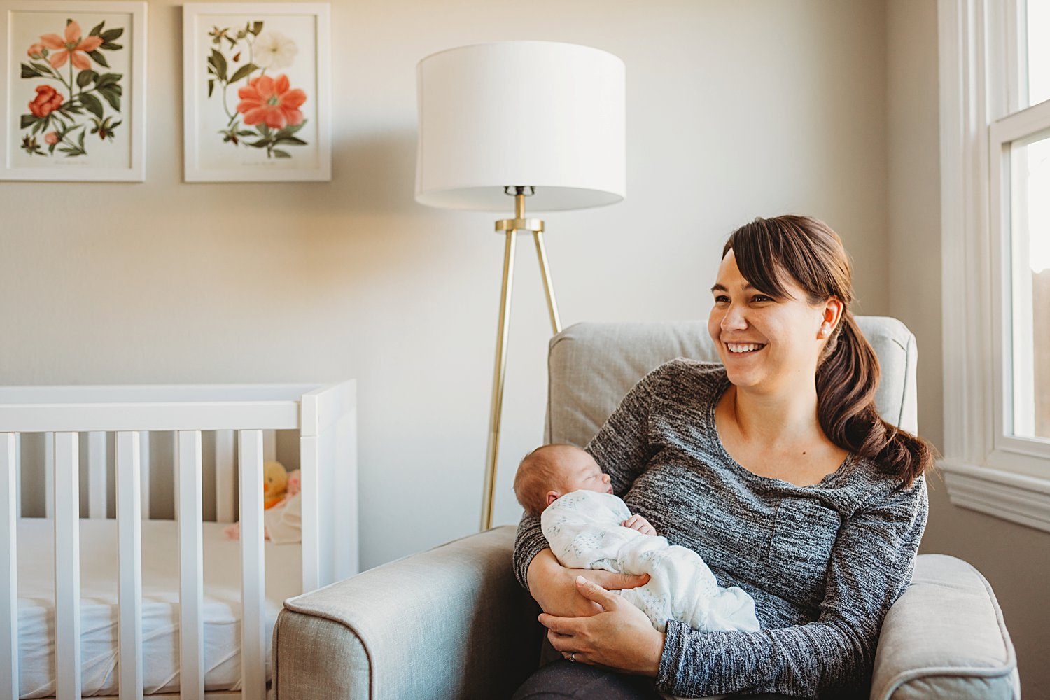 Mom holding newborn baby girl in arms while sitting in chair in nursery