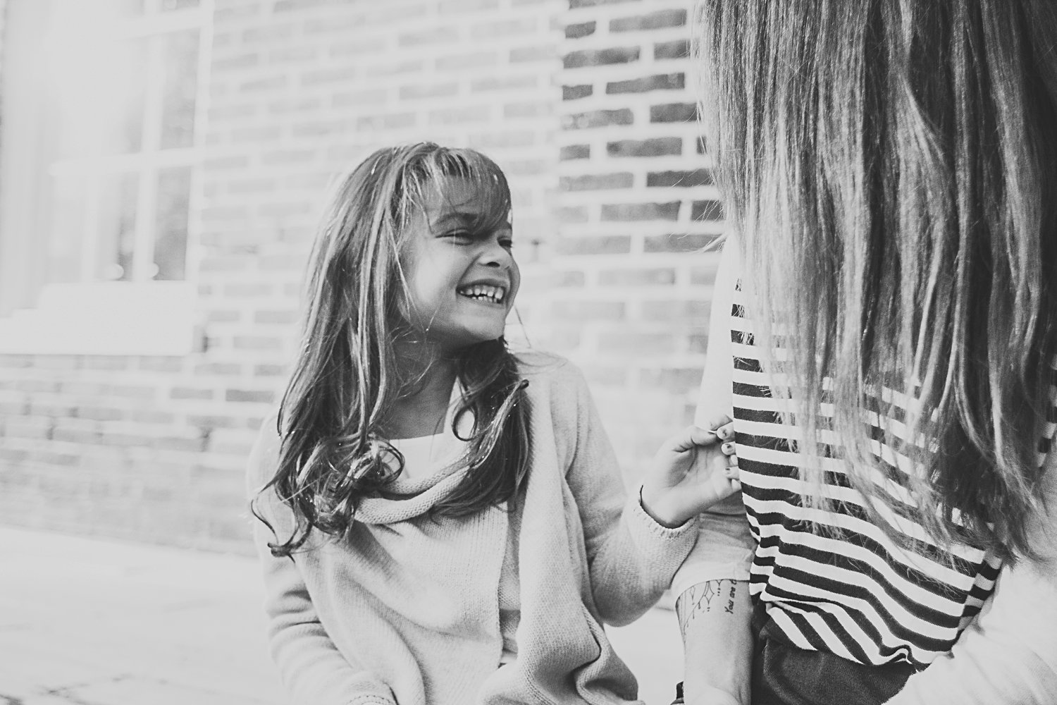 Candid lifestyle portrait of mom and young daughter laughing