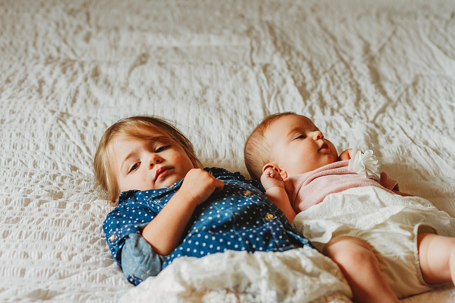 Young children laying on bed for family photos