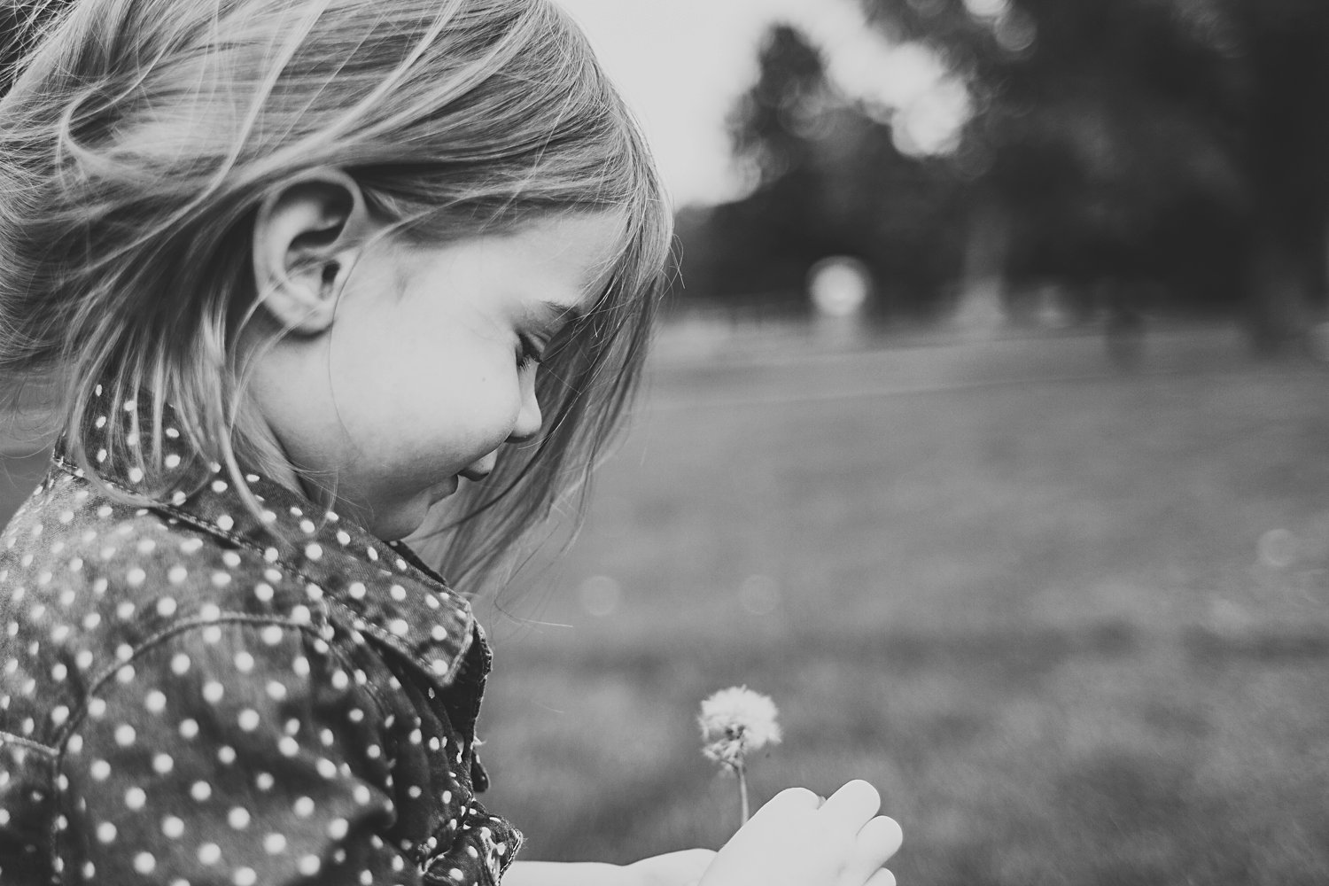 Candid portrait of young girl with dandelion