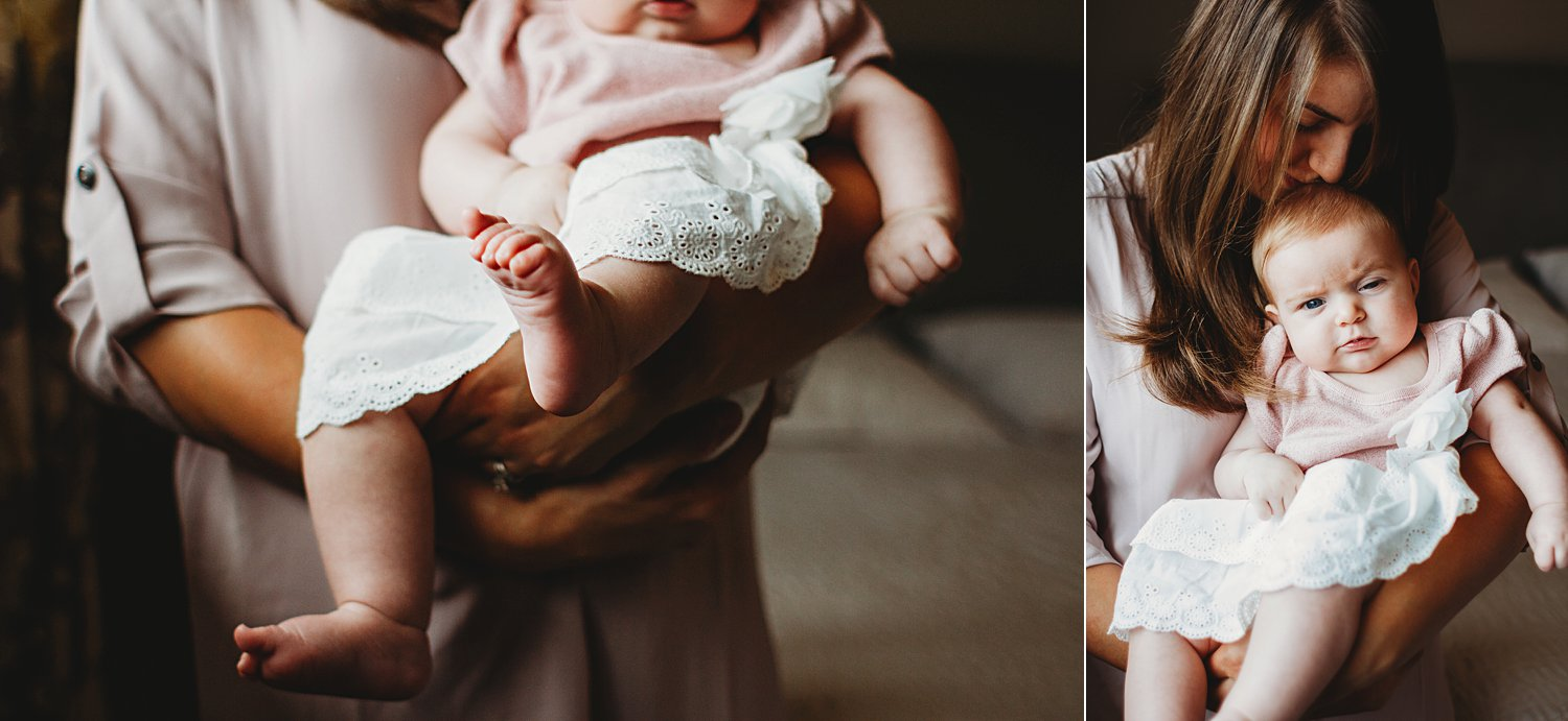 Lifestyle portraits of mom holding baby girl inside