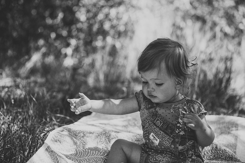 Toddler girl sitting on blanket outside