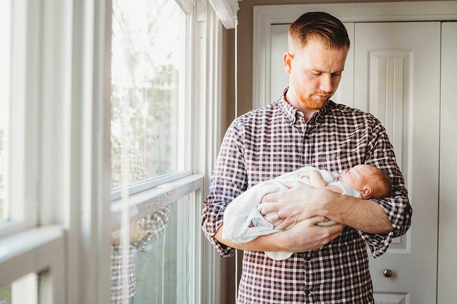 Lifestyle family portrait of dad holding newborn baby