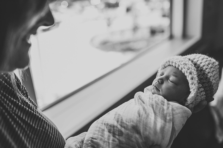 Mom holding newborn baby girl by window