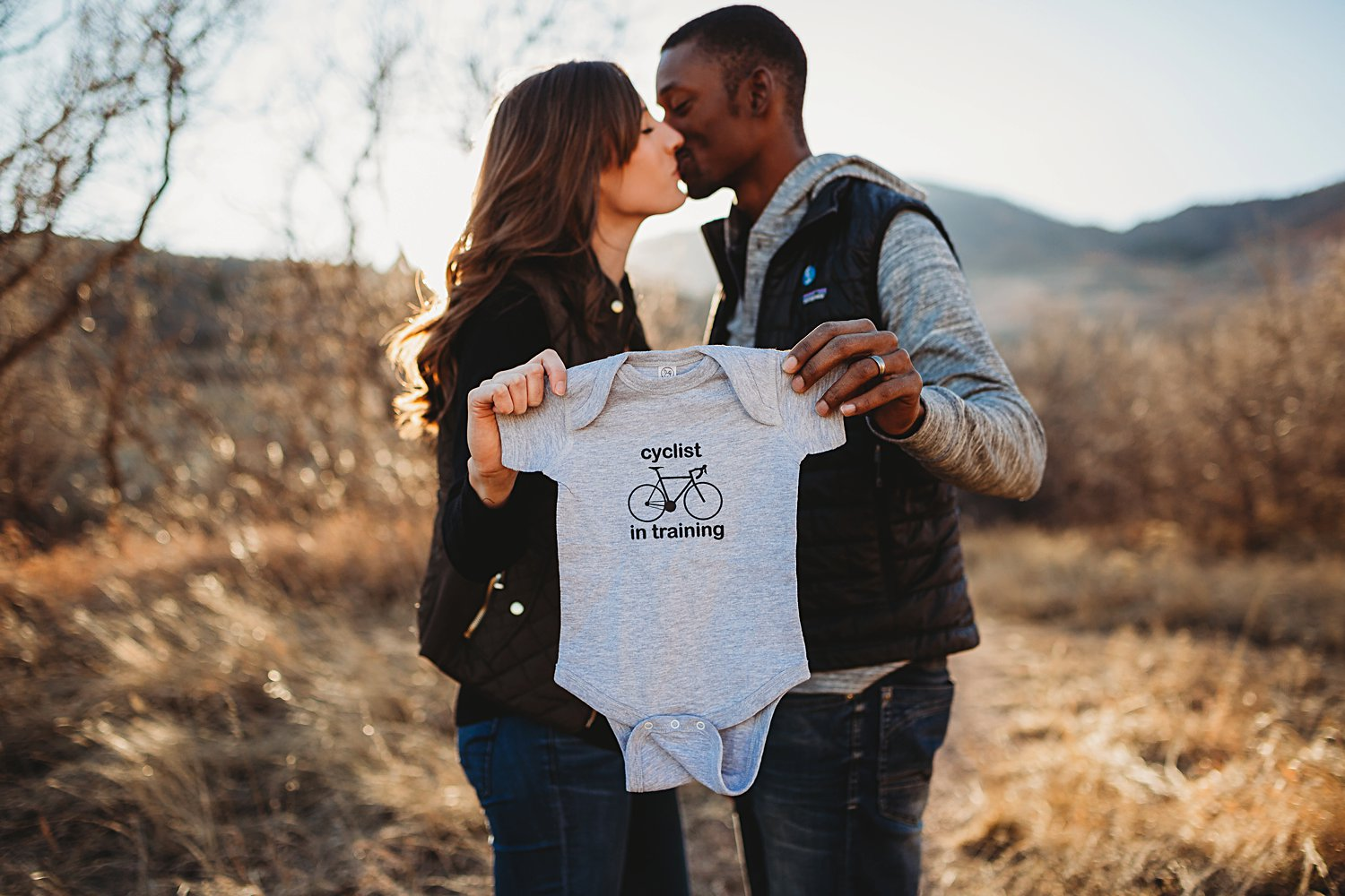Couple kissing and holding up a baby onesie
