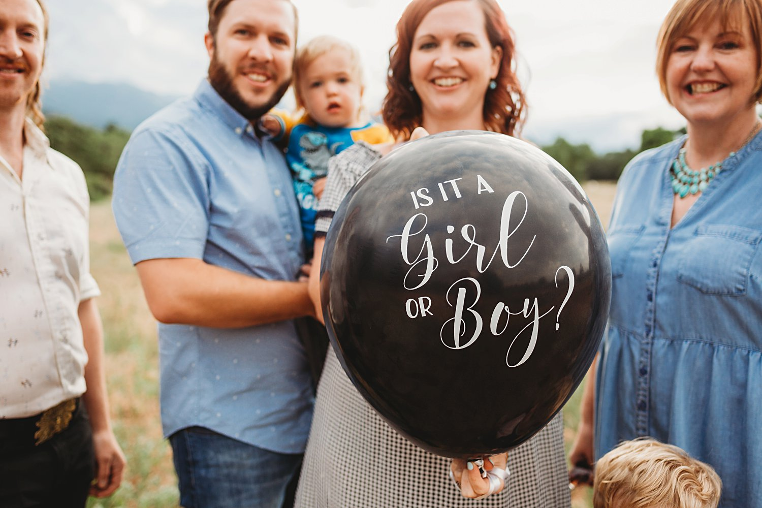 Couple holding balloon that says Is it a girl or a boy