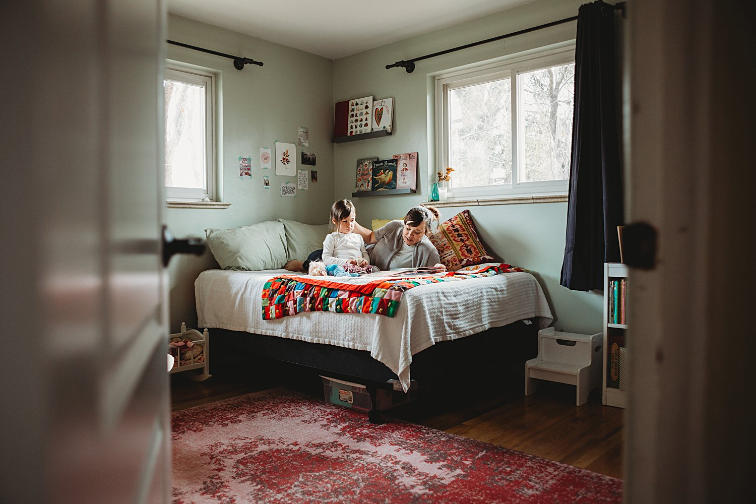 Mom reading with young daughter in bed