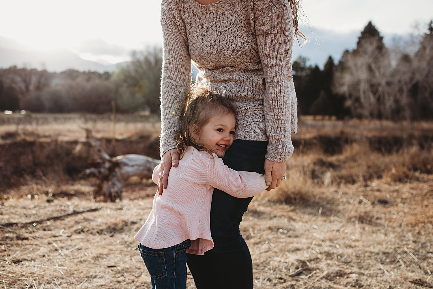 Young daughter hugs mom's legs